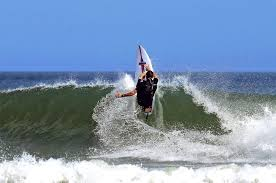 Savage Surfboards rider catching a wave